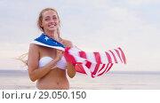 Купить «happy young woman with american flag on beach», видеоролик № 29050150, снято 27 августа 2018 г. (c) Syda Productions / Фотобанк Лори