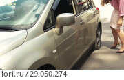 Купить «Woman Got Out Of Car And Looks At Flat Tire», видеоролик № 29050274, снято 27 июня 2018 г. (c) Pavel Biryukov / Фотобанк Лори