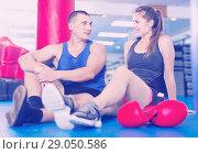 Купить «Female boxer is sitting with man and talking about healthy in gym.», фото № 29050586, снято 21 августа 2017 г. (c) Яков Филимонов / Фотобанк Лори