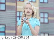 Купить «Красивая и умная школьница блондинка собирает головоломку зеркальный куб, на улице возле школы», фото № 29050854, снято 13 августа 2018 г. (c) Милана Харитонова / Фотобанк Лори