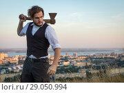 Маньяк над городом, бородатый мужчина с топором на фоне российского города. Стоковое фото, фотограф 1Andrey Милкин / Фотобанк Лори