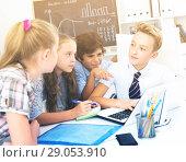 Купить «Boys and girls talking near the notebook», фото № 29053910, снято 12 октября 2017 г. (c) Яков Филимонов / Фотобанк Лори