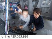 Купить «kids look for a way out in quest room bunker», фото № 29053926, снято 21 октября 2017 г. (c) Яков Филимонов / Фотобанк Лори
