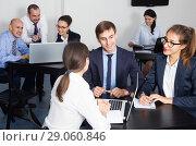 Купить «Smiling coworkers with laptops having a productive day», фото № 29060846, снято 28 октября 2016 г. (c) Яков Филимонов / Фотобанк Лори