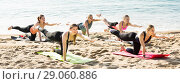 Купить «Group of sporty girls practicing various yoga positions during training on beach», фото № 29060886, снято 22 мая 2017 г. (c) Яков Филимонов / Фотобанк Лори