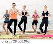Купить «Group of sporty girls practicing various yoga positions during training on beach», фото № 29060962, снято 22 мая 2017 г. (c) Яков Филимонов / Фотобанк Лори