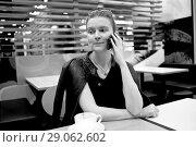 Купить «Девушка с мобильным телефоном в кафе», фото № 29062602, снято 26 августа 2018 г. (c) Victoria Demidova / Фотобанк Лори