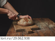 Купить «on wooden board man slicing fresh organic bread», фото № 29062938, снято 21 апреля 2017 г. (c) Ярослав Данильченко / Фотобанк Лори
