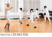 Купить «Coaches demonstrating to young athletes attack movements with rapier during fencing workout», фото № 29063926, снято 30 мая 2018 г. (c) Яков Филимонов / Фотобанк Лори