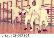 Купить «Focused boys fencers attentively listening to professional fencing coach in gym», фото № 29063954, снято 30 мая 2018 г. (c) Яков Филимонов / Фотобанк Лори
