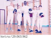 Купить «Group portrait of young fencers with coaches holding rapiers in training room», фото № 29063962, снято 30 мая 2018 г. (c) Яков Филимонов / Фотобанк Лори