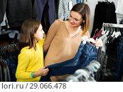Купить «Mother and daughter deciding on new jeans», фото № 29066478, снято 22 сентября 2018 г. (c) Яков Филимонов / Фотобанк Лори