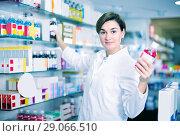 Купить «Customer girl is browsing rows of body care products», фото № 29066510, снято 31 января 2017 г. (c) Яков Филимонов / Фотобанк Лори