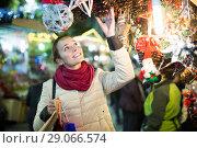 Купить «woman choosing Christmas decoration at market in evening time», фото № 29066574, снято 18 октября 2018 г. (c) Яков Филимонов / Фотобанк Лори
