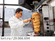 Купить «chef slicing doner meat from spit at kebab shop», фото № 29066694, снято 7 декабря 2017 г. (c) Syda Productions / Фотобанк Лори