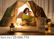 Купить «happy family reading book in kids tent at home», фото № 29066710, снято 27 января 2018 г. (c) Syda Productions / Фотобанк Лори