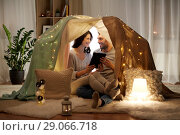 Купить «happy couple with tablet pc in kids tent at home», фото № 29066718, снято 27 января 2018 г. (c) Syda Productions / Фотобанк Лори