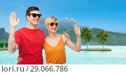 Купить «couple in sunglasses waving hands over bora bora», фото № 29066786, снято 30 июня 2018 г. (c) Syda Productions / Фотобанк Лори