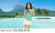 Купить «teenage girl with film camera over bora bora beach», фото № 29066818, снято 30 июня 2018 г. (c) Syda Productions / Фотобанк Лори