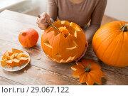 Купить «close up of woman carving halloween pumpkin», фото № 29067122, снято 15 сентября 2017 г. (c) Syda Productions / Фотобанк Лори