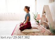 Купить «woman meditating in lotus pose at yoga studio», фото № 29067382, снято 21 июня 2018 г. (c) Syda Productions / Фотобанк Лори