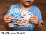 Купить «Маленький ребёнок держит в руках российские банкноты», эксклюзивное фото № 29068226, снято 10 сентября 2018 г. (c) Игорь Низов / Фотобанк Лори