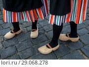 Купить «Девушка традиционной голландской одежде и деревянных башмаках (кломпах) стоит на булыжной мостовой», фото № 29068278, снято 2 сентября 2018 г. (c) Николай Винокуров / Фотобанк Лори