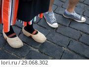 Купить «Девушка в традиционной голландской одежде и деревянных башмаках (кломпах) и мужчина в современных кедах стоят на булыжной мостовой в центре европейского города», фото № 29068302, снято 2 сентября 2018 г. (c) Николай Винокуров / Фотобанк Лори