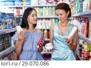 Jolly woman and girl looking haircare products. Стоковое фото, фотограф Яков Филимонов / Фотобанк Лори