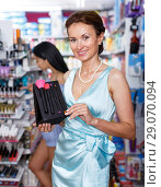 Купить «Attractive mature woman looking for brush set at store», фото № 29070094, снято 21 июня 2018 г. (c) Яков Филимонов / Фотобанк Лори