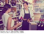 Купить «portrait of male seller showing bottle of wine to female custom», фото № 29070186, снято 21 октября 2018 г. (c) Яков Филимонов / Фотобанк Лори