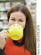 Купить «Женщина пьет из желтой чашки с нарисованным смайликом», фото № 29070574, снято 14 февраля 2014 г. (c) Кекяляйнен Андрей / Фотобанк Лори