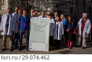 Купить «Doctors in scrubs and lab coats at the gates of Downing Street with a person-sized prescription for the Prime Minister to tackle illegal air pollution...», фото № 29074462, снято 10 мая 2017 г. (c) age Fotostock / Фотобанк Лори