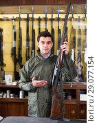 Купить «Portrait of handsome confident man showing rifle», фото № 29077154, снято 11 декабря 2017 г. (c) Яков Филимонов / Фотобанк Лори