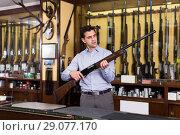 Купить «Male standing with shotgun indoors in hunting shop», фото № 29077170, снято 11 декабря 2017 г. (c) Яков Филимонов / Фотобанк Лори
