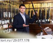 Купить «Salesman showing rifle», фото № 29077178, снято 11 декабря 2017 г. (c) Яков Филимонов / Фотобанк Лори
