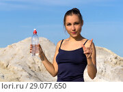 Young slender athletic girl after playing sports outdoors holds a plastic water bottle and gestures to emphasize the importance of drinking water. Стоковое фото, фотограф Евгений Харитонов / Фотобанк Лори