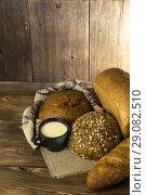 Купить «Food. Assortment of baked bread and milk on a wooden table background.», фото № 29082510, снято 25 августа 2018 г. (c) Светлана Евграфова / Фотобанк Лори