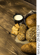 Food. Rural breakfast. Assortment of fresh bread baked in a bakery, biscuits and a mug with milk on a wooden table background. Стоковое фото, фотограф Светлана Евграфова / Фотобанк Лори