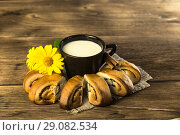Купить «Food. Baking of confectionery. Fresh baked bakery with poppy seeds and a cup of milk for breakfast on the background of the texture of a wooden table», фото № 29082534, снято 25 августа 2018 г. (c) Светлана Евграфова / Фотобанк Лори