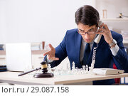 Купить «Young lawyer playing chess to train his court strategy and tacti», фото № 29087158, снято 31 июля 2018 г. (c) Elnur / Фотобанк Лори