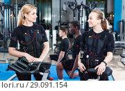 Купить «Two fit woman communicating during electric muscle stimulation workout in gym», фото № 29091154, снято 16 апреля 2018 г. (c) Яков Филимонов / Фотобанк Лори