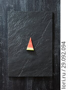 Купить «A piece of fresh watermelon on a black slate on a dark concrete background with copy space. Vitamin dessert. Top view», фото № 29092094, снято 24 июля 2018 г. (c) Ярослав Данильченко / Фотобанк Лори