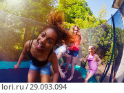 Купить «African girl playing with friends on trampoline», фото № 29093094, снято 20 мая 2018 г. (c) Сергей Новиков / Фотобанк Лори