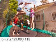 Купить «Happy friends bouncing on the outdoor trampoline», фото № 29093118, снято 20 мая 2018 г. (c) Сергей Новиков / Фотобанк Лори