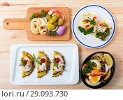 Купить «Deliciously different dishes with calamari and sepia served at desk», фото № 29093730, снято 21 сентября 2018 г. (c) Яков Филимонов / Фотобанк Лори