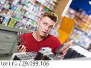 Купить «Surprised guy choosing DVD», фото № 29099106, снято 15 февраля 2018 г. (c) Яков Филимонов / Фотобанк Лори
