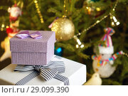 Купить «Gift boxes with bows on the lids under a Christmas tree in New Year Eve», фото № 29099390, снято 1 января 2018 г. (c) Георгий Дзюра / Фотобанк Лори