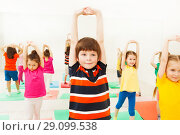 Купить «Boy stretching hands during sports lesson in gym», фото № 29099538, снято 15 апреля 2017 г. (c) Сергей Новиков / Фотобанк Лори