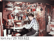 Купить «Smiling male worker working on stitches for belt», фото № 29103622, снято 22 марта 2019 г. (c) Яков Филимонов / Фотобанк Лори
